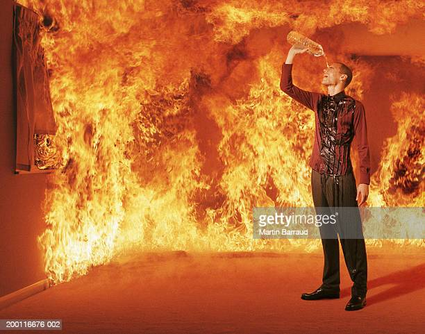Young man pouring water over head in burning room (Digital Composite)