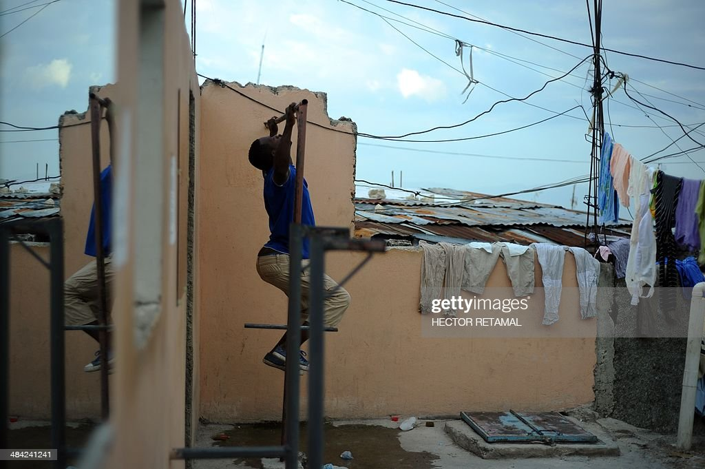 A young man practices exercises his arms at a gym in the Jalousie neighborhood of Petionville, a suburb of Port-au-Prince on April 11, 2014. AFP PHOTO/Hector RETAMAL