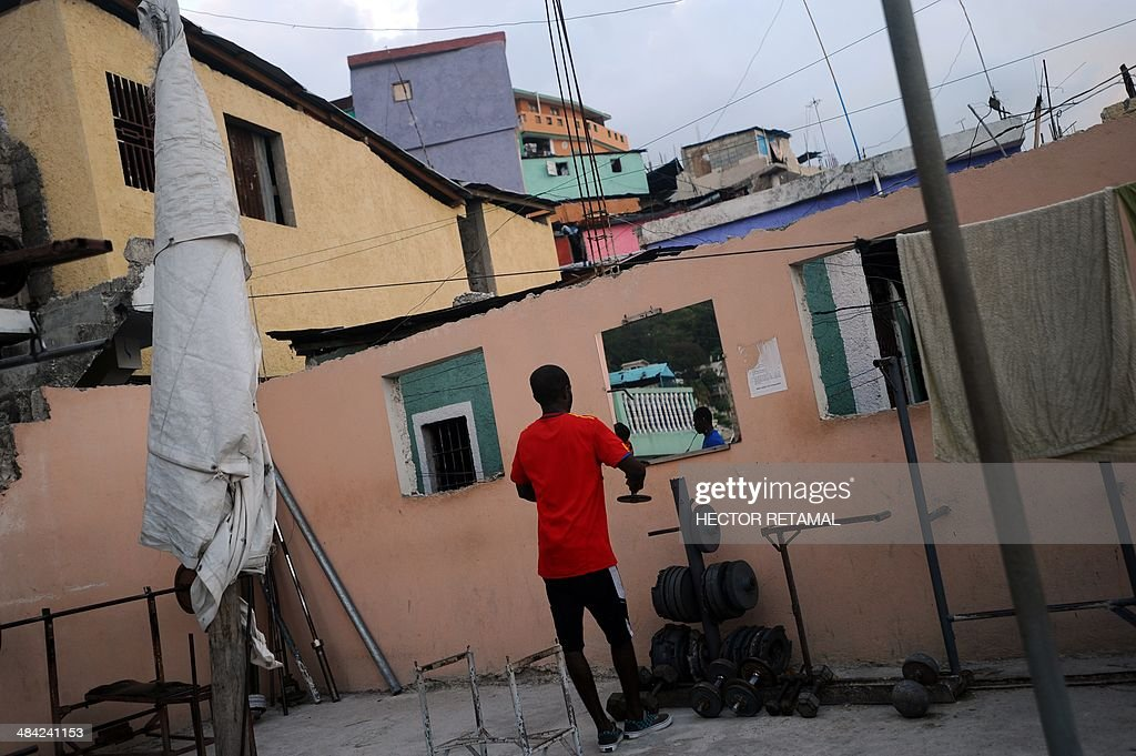 A young man practices weightlifting at a gym in the Jalousie neighborhood of Petionville, a suburb of Port-au-Prince on April 11, 2014. AFP PHOTO/Hector RETAMAL