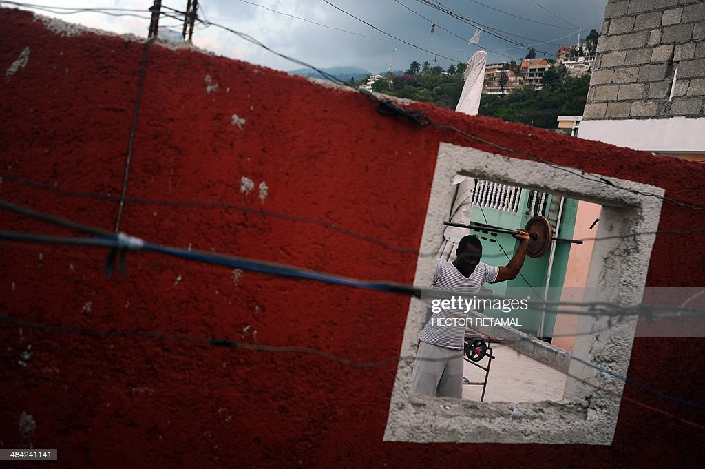 A young man practices weightlifting in a gym in the Jalousie neighborhood of Petionville, a suburb of Port-au-Prince on April 11, 2014. AFP PHOTO/Hector RETAMAL