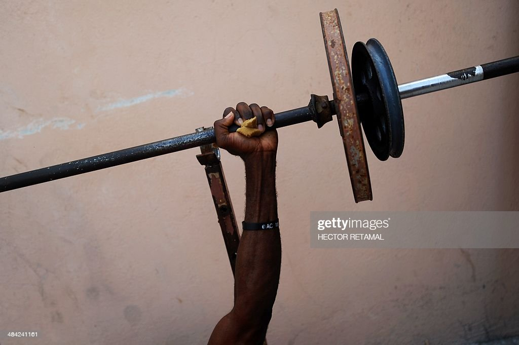 A young man practices weightlifting on the roof of a gym in the Jalousie neighborhood of Petionville, a suburb of Port-au-Prince on April 11, 2014. AFP PHOTO/Hector RETAMAL