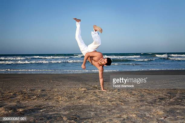 Young man practicing capoeira on beach