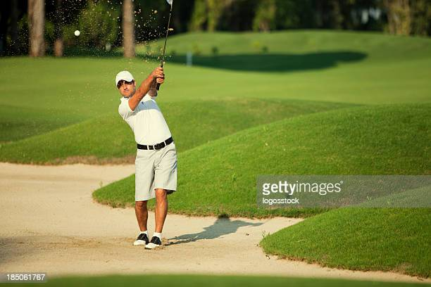 Young man practicing his swing in green golf course