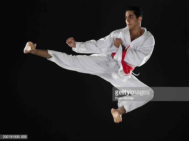 Giovane uomo di praticare arti marziali saltando in midair