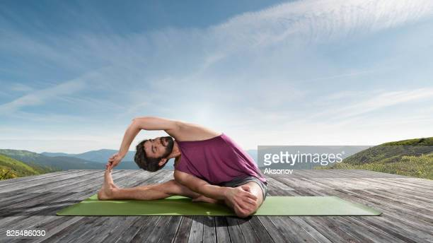 Young man practicing outdoors yoga. Head-to-Knee Forward Bend