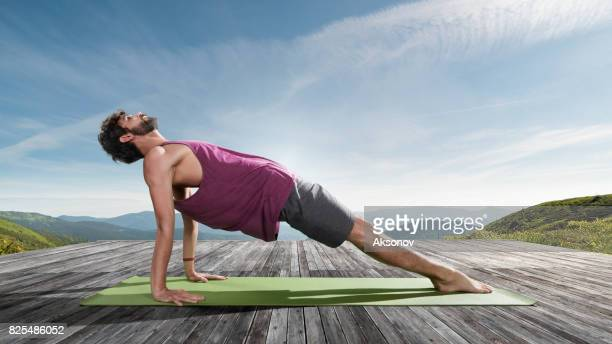 Young man practicing outdoors yoga. Table top