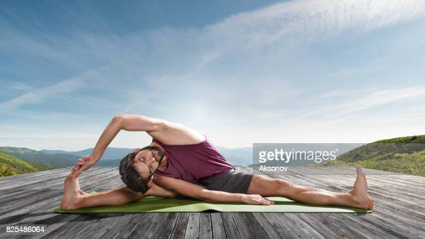 Young man practicing outdoors yoga. Wide-Angle Seated Forward Bend