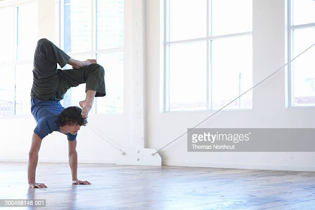Young man practicing yoga, performing handstand