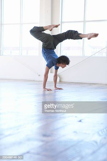Young man practicing yoga, performing handstand, side view