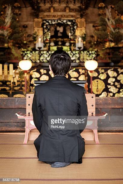 Young Man Praying in Buddhist Temple