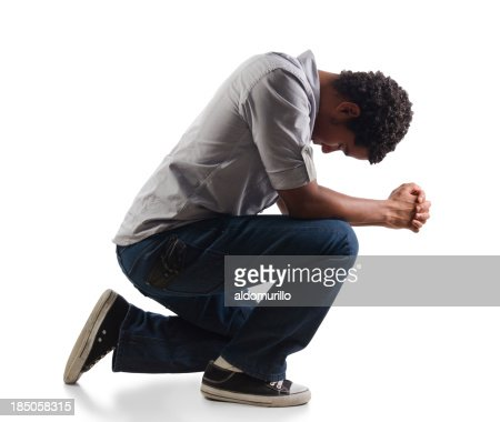 Young man praying on his knees