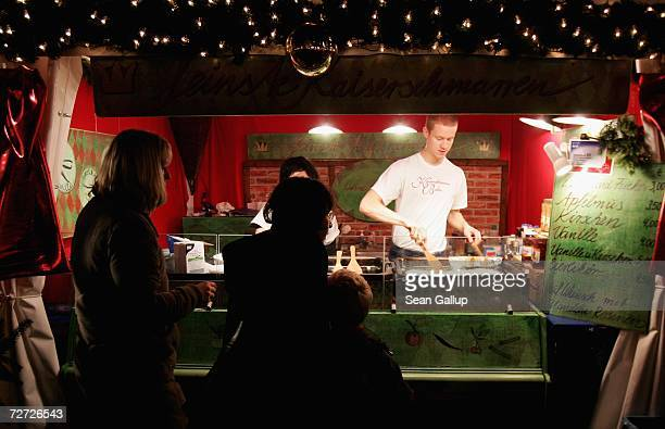 A young man prepares Kaiserschmarrn which is shredded pancakes with raisins that are sprinkled with powdered sugar and served with applesauce at the...