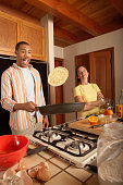 Young man preparing an omelet in the kitchen with his wife