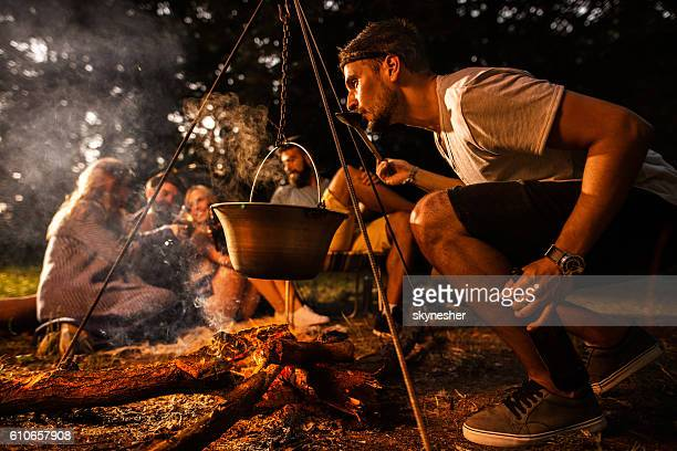 Young man preparing food while camping with his friends.