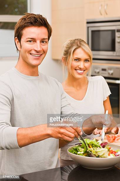 Young man preparing salad and woman standing beside