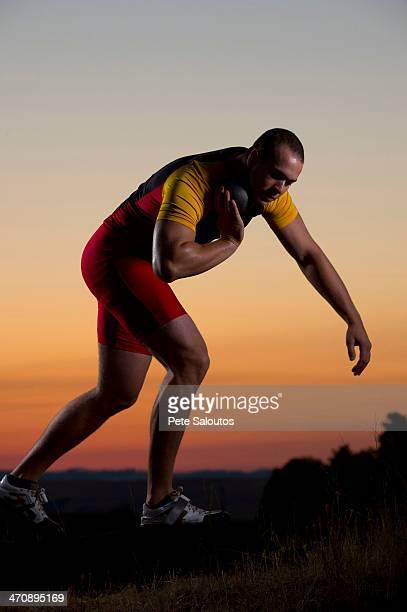 Young man preparing to throw shot put at sunset