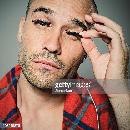 Young man pulling on eyelashes