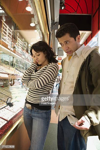 Young man pulling out his empty pocket with a young woman looking sad in a jewelry store