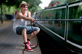 Young man pulling rope of canal canal boat