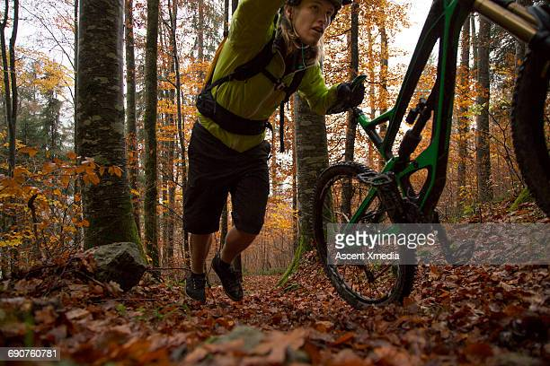 Young man pushes mtn bike through autumn forest