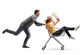 Young man pushing a shopping cart with a woman with a popcorn box riding inside isolated on white background