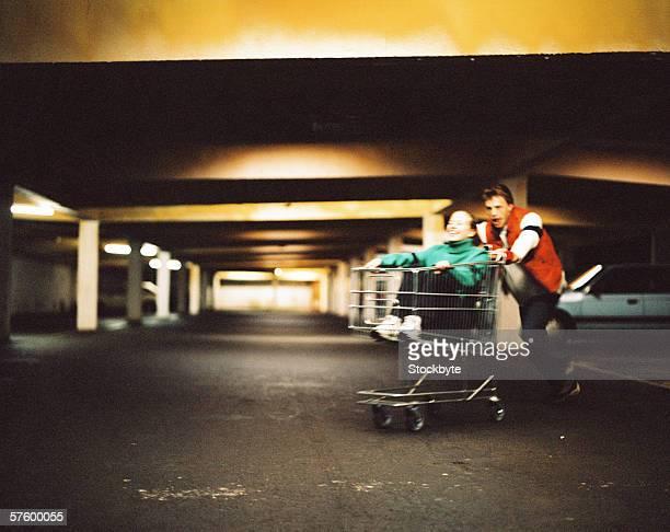 Young man pushing a young woman in a shopping cart