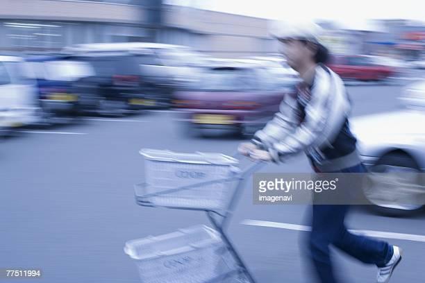 Young Man Pushing an Empty Shopping Cart