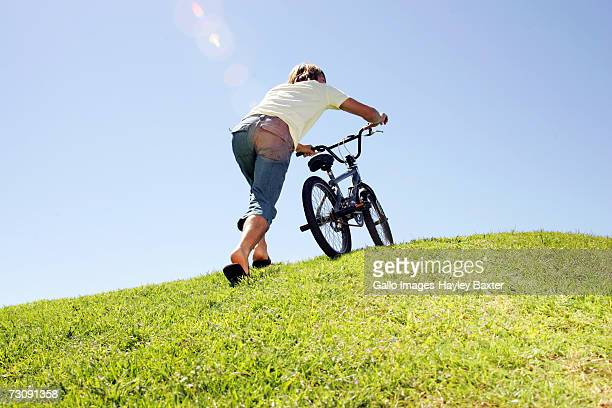 Young man pushing bicycle up hillside