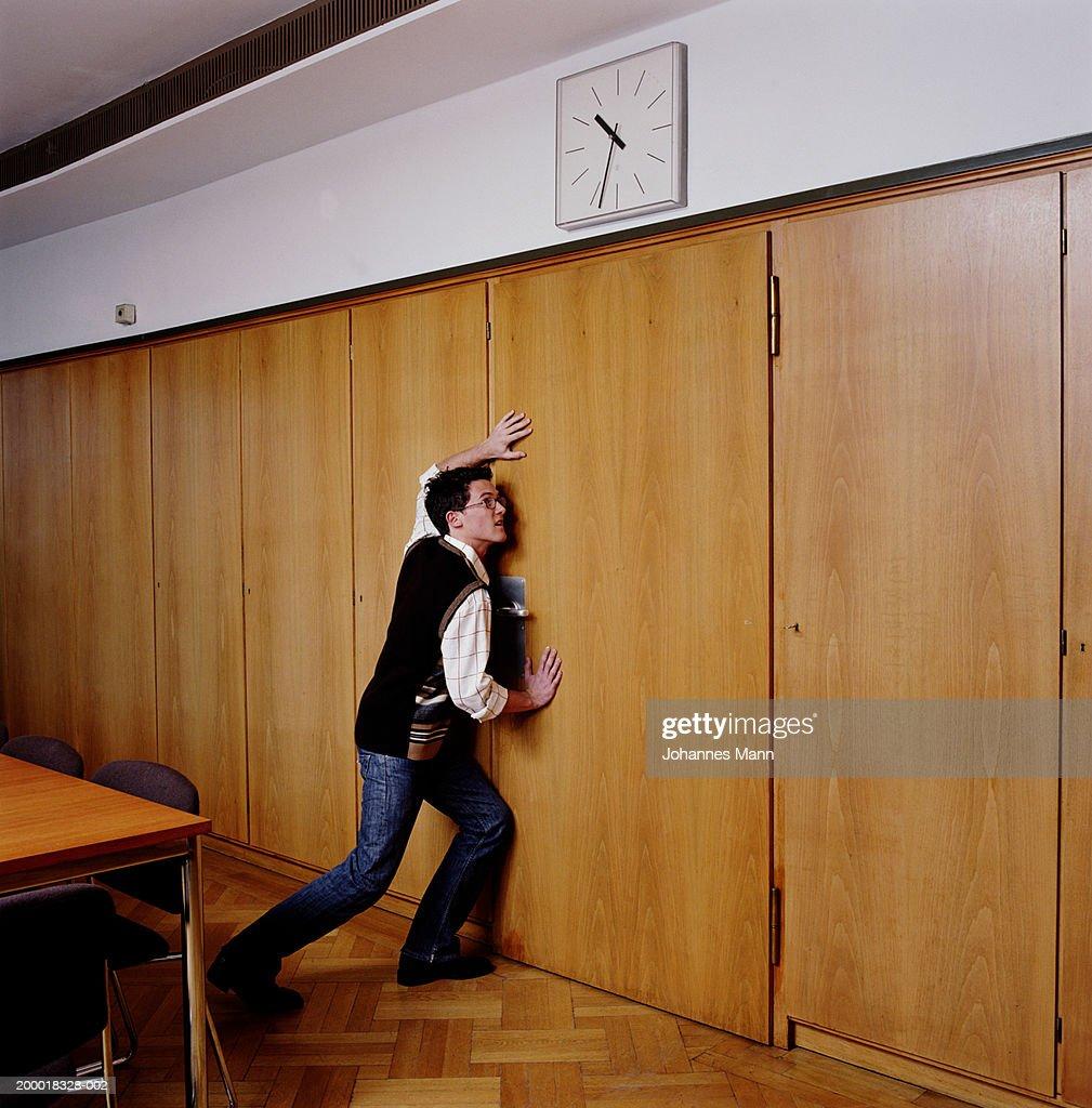 Young man pushing door shut : Stock Photo
