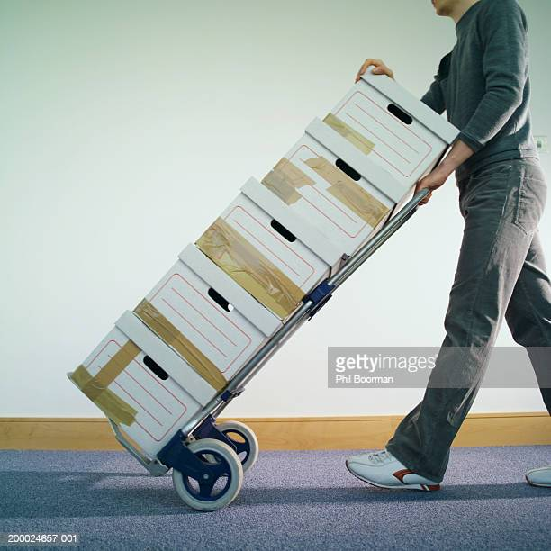 Young man pushing sack truck stacked with packing boxes