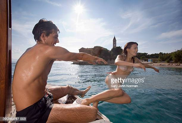 Young man pushing woman into ocean from boat, side view