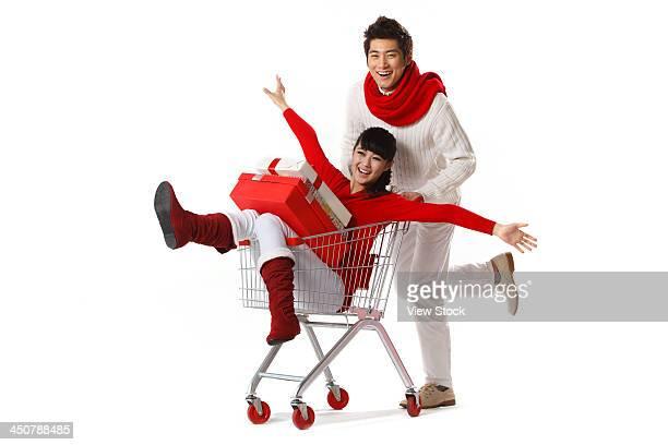 Young man pushing young woman in shopping cart