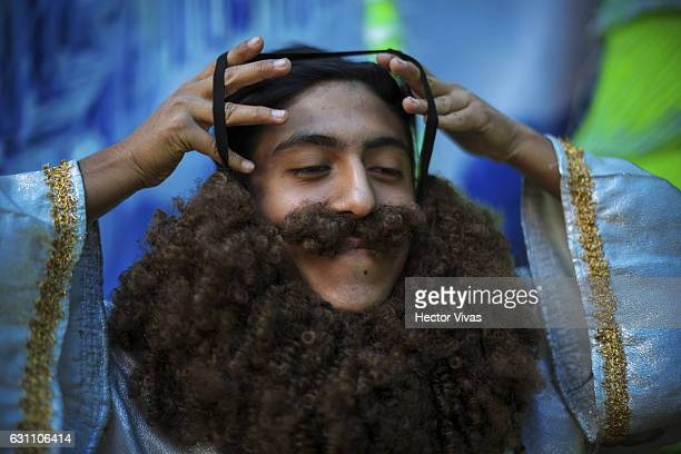 A young man puts on a fictitious beard during the Three Wise Man celebration on January 06 2017 in Mexico City Mexico The Three Wise Man day also...