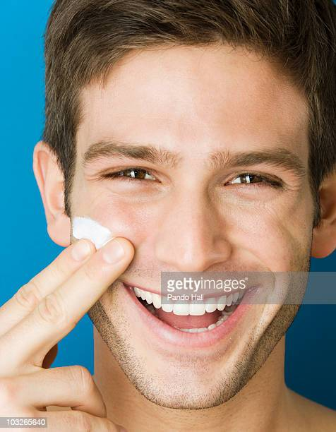 Young man putting cream on his face, smiling