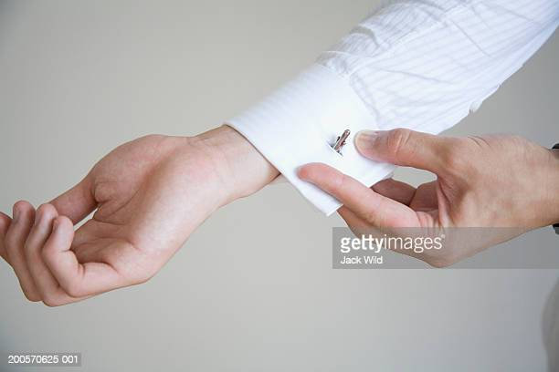 Young man putting cuff links, close-up