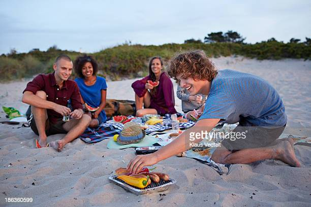 Young man putting food on the grill at beach