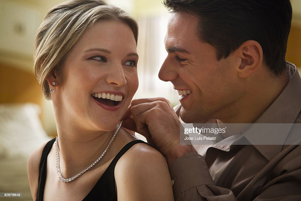 Young man putting necklace on young woman's neck : Stock Photo