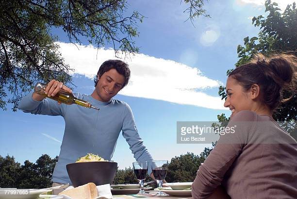 Young man putting olive oil on pasta