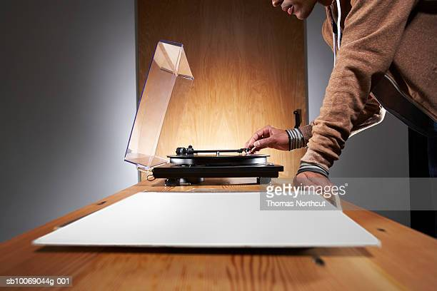 Young man putting stylus on record player, mid section