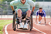 Disabled athlete in wheelchair on running track with his son