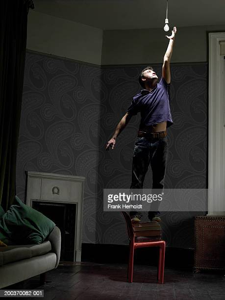 Young man reaching for light bulb