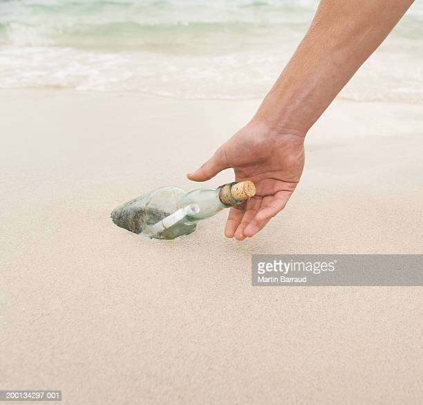 Young man reaching for message in a bottle on beach, close-up