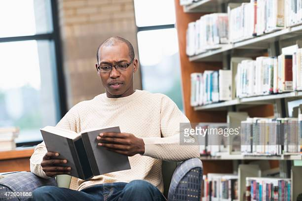Young man reading a book at the library