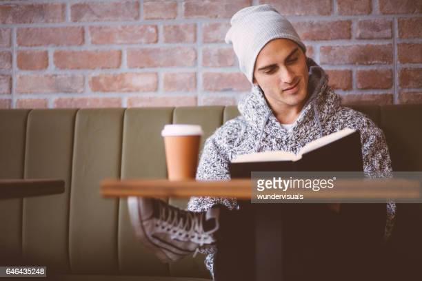 Young man reading a book, drinking coffee in coffee shop