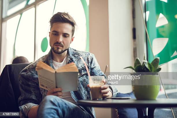 Young man reading a book in a cafe.