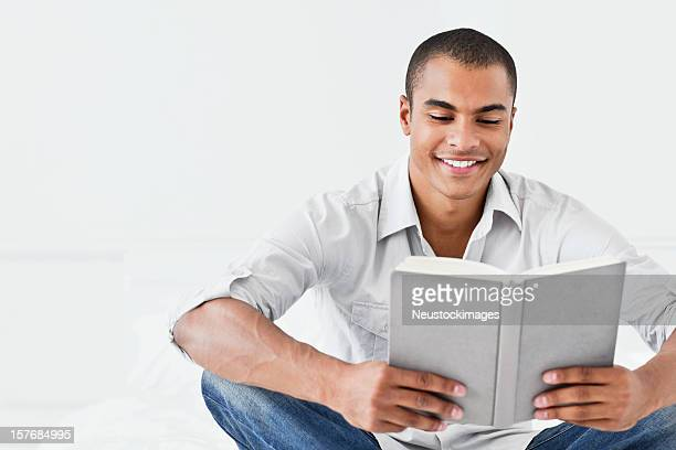 Young Man Reading a Book on His Bed