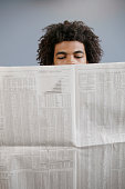 Young man reading a newspaper