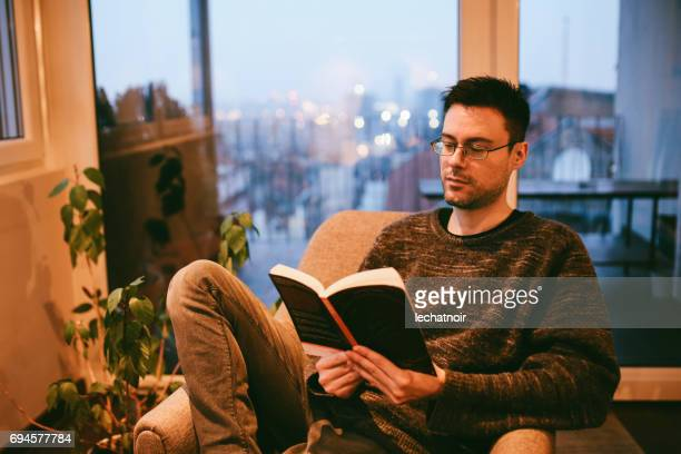 Young man reading and relaxing at home