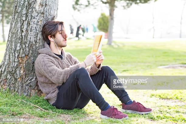 Young man reading book and sitting on grass