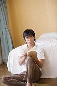 Young man reading book by bed